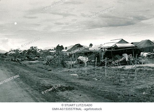 Makeshift homes in a traditional village beside a road during the Vietnam War, 1968. ()