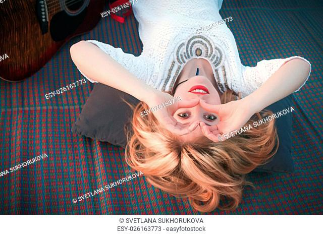 Beautiful girl lying on a mat view upside down, smiling and looking through her hands in the shape of a heart
