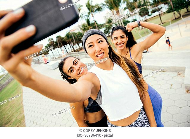 Three female friends, wearing sports clothing, taking selfie using smartphone, South Point Park, Miami Beach, Florida, USA