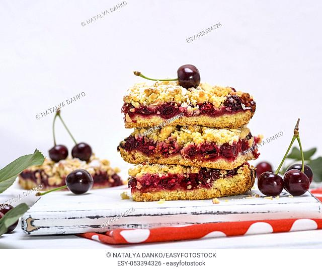 a stack of baked slices of a pie with cherry berries on a white wooden board, white background