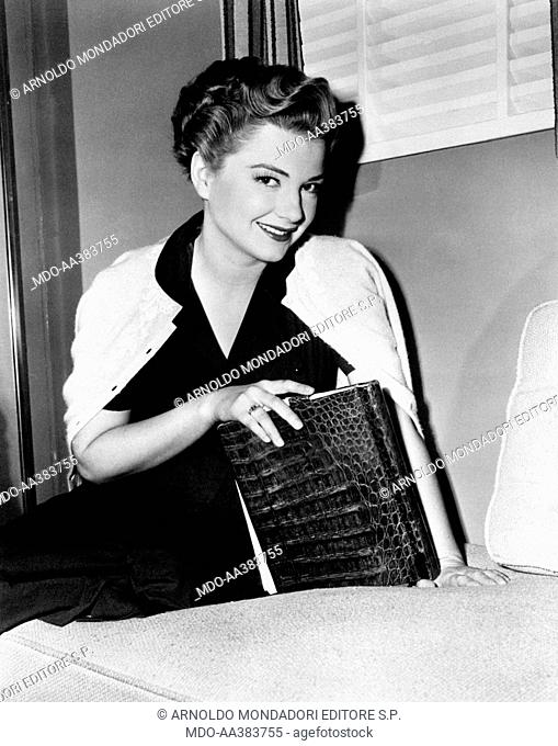 Anne Baxter seated on a sofa. American actress Anne Baxter sitting on a sofa holding an alligator bag in her right hand. 1950s
