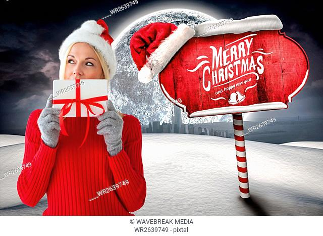 Beautiful woman in santa costume holding christmas gift