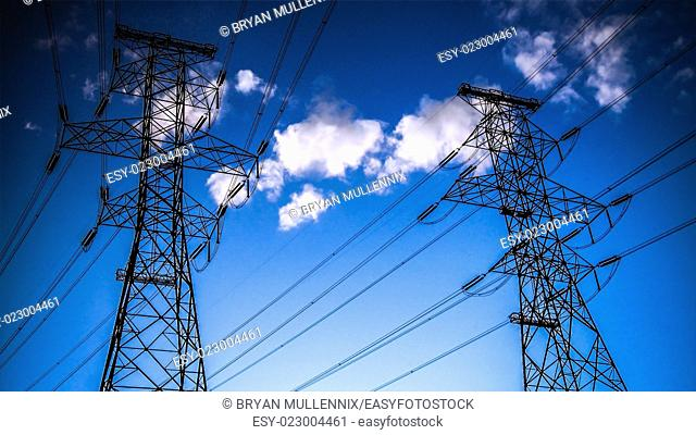 High voltage power lines and towers in silhouette against sunset sky and clouds