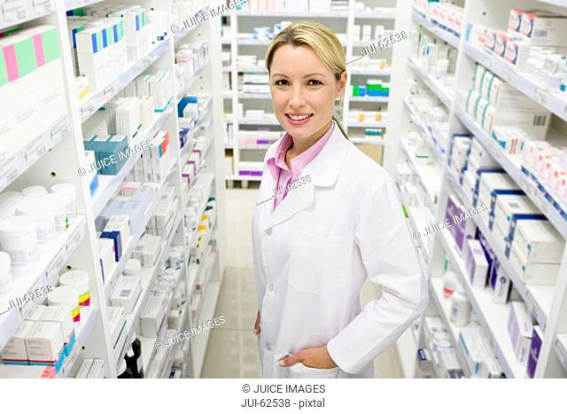 Pharmacist smiling with hands in pockets in pharmacy