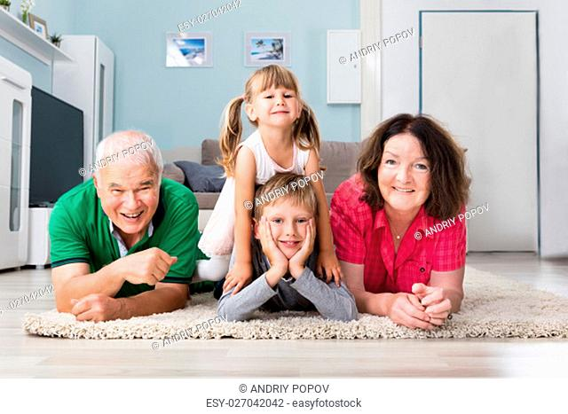 Happy Family Cuddling While Lying On Carpet At Home