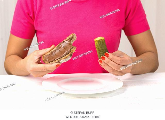 Young woman eating pickled cucumber and slice of bread with chocolate cream
