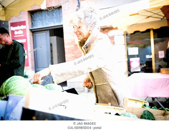 Mature female shopper buying vegetables at local french market