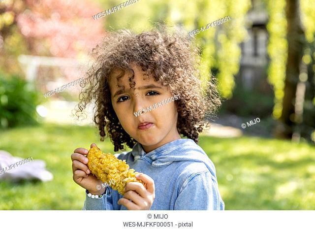 Portrait of boy eating a corn cob in garden
