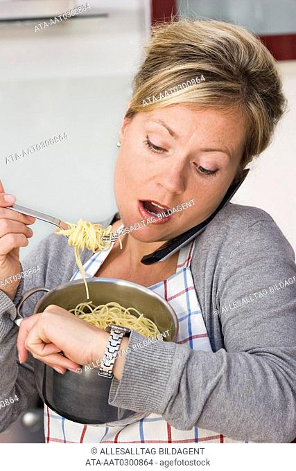 Stressed woman eating noodles