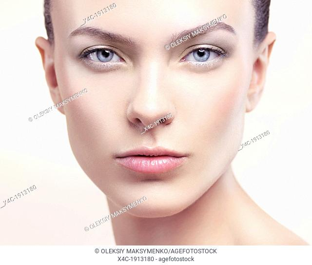 Closeup beauty portrait of a young woman face with natural makeup and clean porcelain skin
