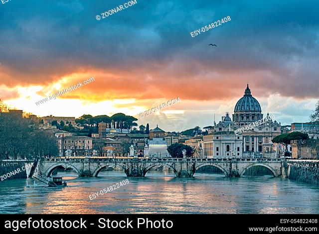 St. Peter's cathedral and Tiber river with high water at evening with dramatic sunset sky. Saint Peter Basilica in Vatican city with Saint Angelo Bridge in Rome