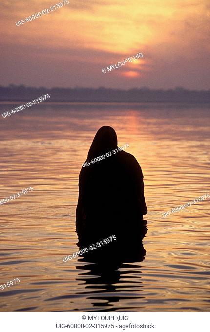 A faithful HINDU bathes in the GANGES RIVER at SUNRISE - VARANASI BENARES, INDIA