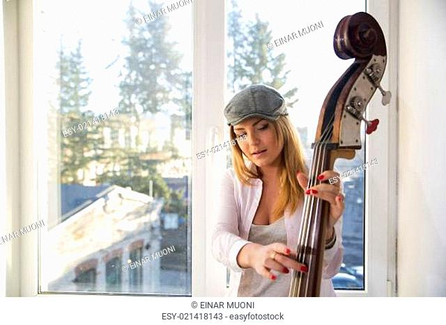 Woman with hat pulls strings of contrabass