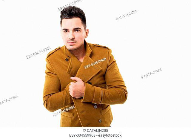 A handsome male model with dark hair wearing a fancy jacket while posing in a photo studio, isolated on a white background