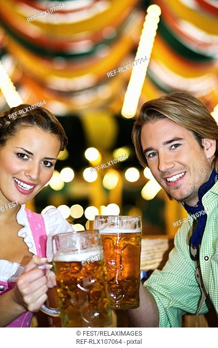 Young couple drinking Beer in beer tent at Oktoberfest, Munich, Germany