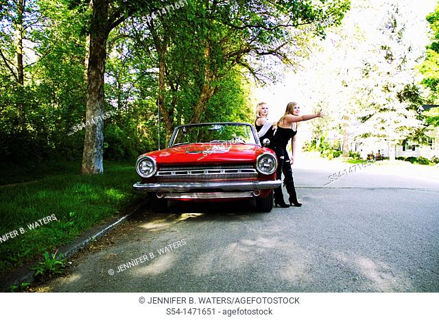 Two young women with a 1964 Dodge Dart in 1980s makeup, hitchhiking