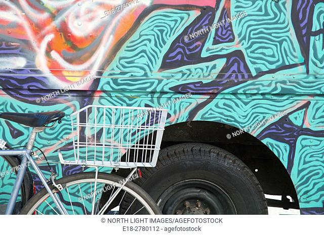 Canada, BC, Vancouver. Bicycle parked beside colorfully painted vehicle
