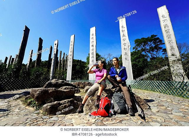 Hikers rest in front of wooden steles at Wisdom Path, Lantau Island, Hong Kong, China