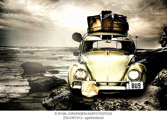 Vintage 1960 VW Beetle on a rocky Australian landscape coast packed to the rafters with vintage luggage. The travel bug