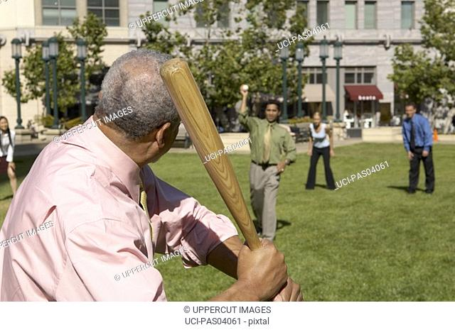 Businesspeople playing baseball outdoors