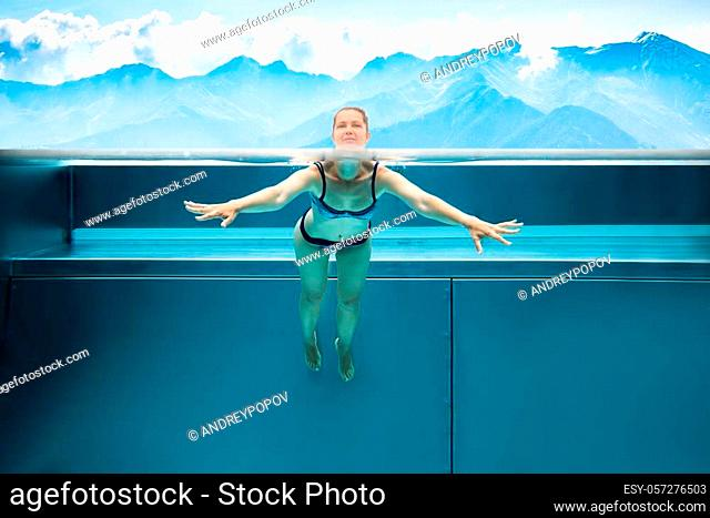 Above Below Water Photo Of Woman Swimming In Pool In Mountains