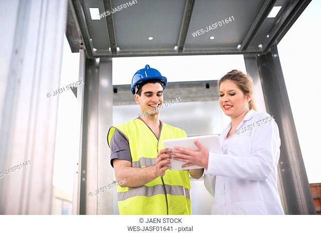 Scientist and factory worker looking at digital tablet