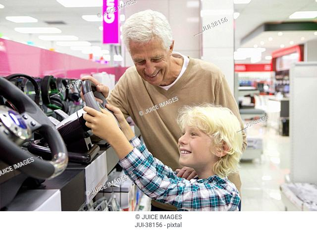 Grandfather watching grandson play with video game steering wheel in electronics store