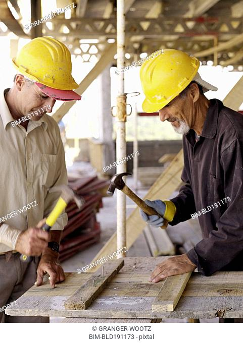 Hispanic workers using hammers at construction site