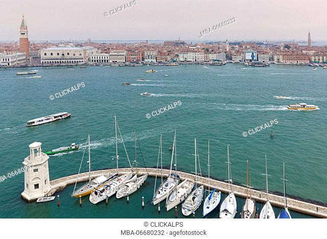 Europe, Italy, Veneto, island of San Giorgio Maggiore. One of the headlights of the dock and some moored boats, on the background St