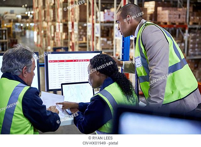 Managers meeting reviewing paperwork at laptop and computer in distribution warehouse