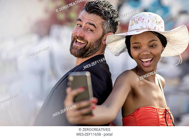 Happy man and woman taking a selfie with cell phone