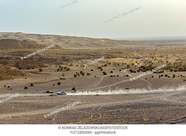 Car on the road on Maranjab Desert located in Aran va bidgol County in Iran