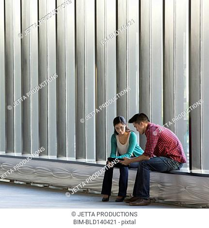 Business people using digital tablet on windowsill