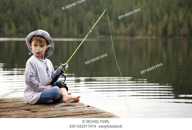 a small boy fishing off an old wooden dock looking behind him because something startled him