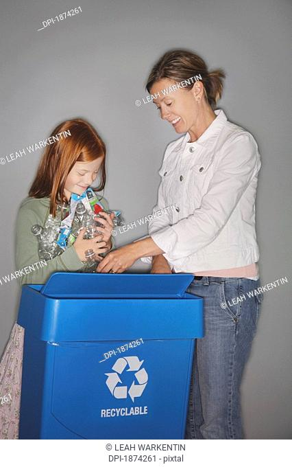 edmonton, alberta, canada, a mother and daughter putting bottles and juice boxes into a blue recycle box