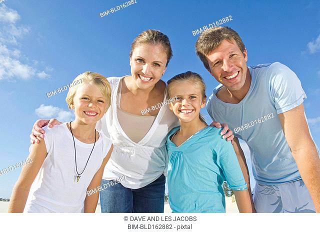 Caucasian parents and children smiling under blue sky