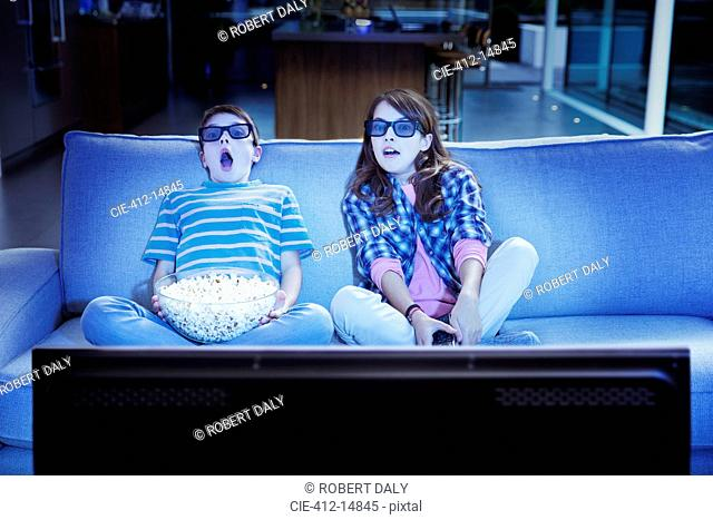 Children watching 3D television in living room