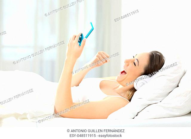 Side view portrait of an excited woman using a smart phone in the bed at home