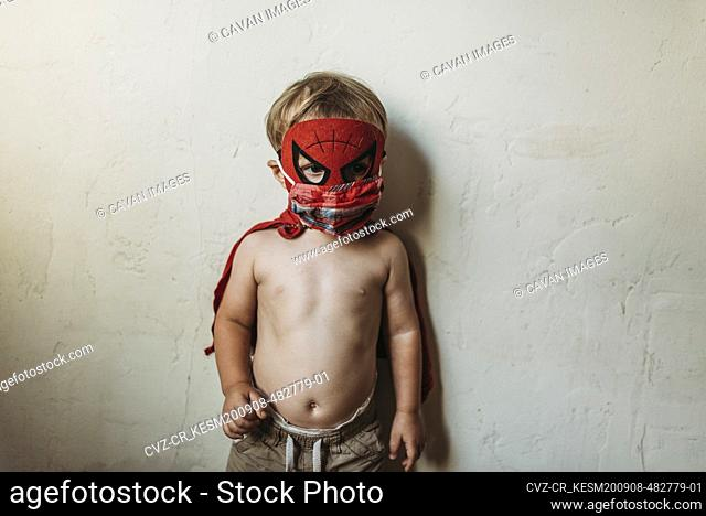 Toddler boy standing in Halloween costume and face mask