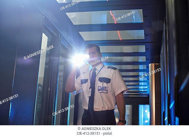 Male security guard with flashlight in server room