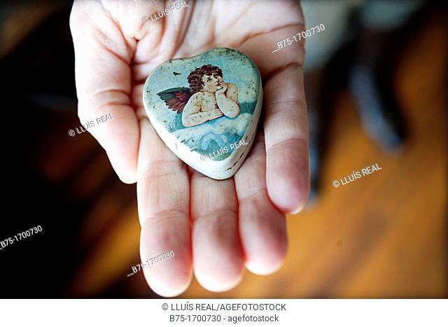 mano ofreciendo cajita con un angel y forma de corazon, amor, offering hand box with an angel and heart shaped, Love