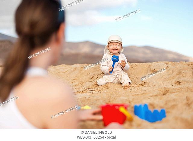 Happy baby girl playing on the beach looking at mother