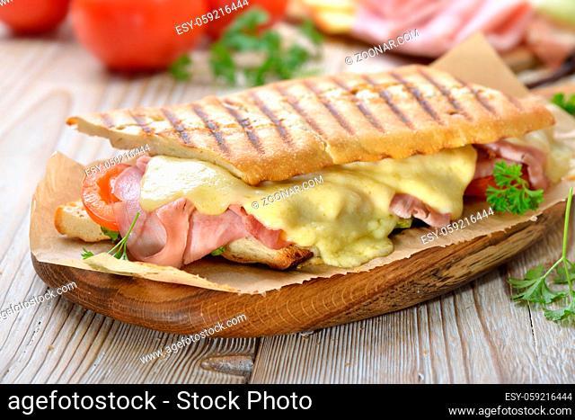 Getoastetes und im Kontaktgrill gepresstes italienisches Panini mit Schinken, Käse , Tomaten und Salat - Pressed and toasted panini with ham, cheese