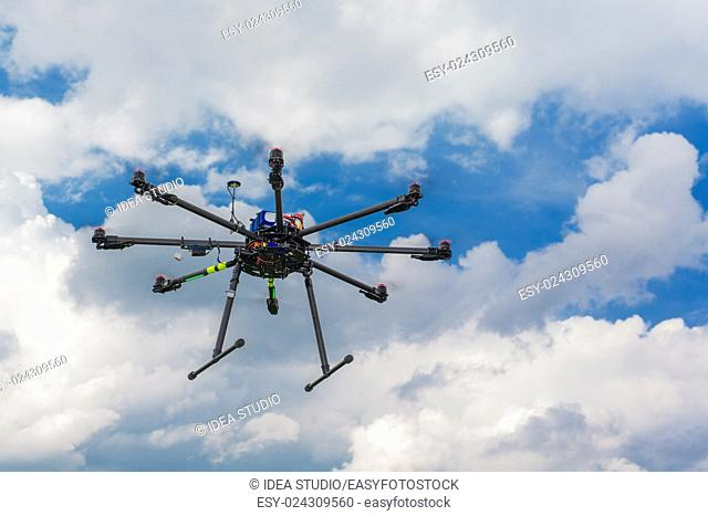 Multicopter in flight on sky and clouds background