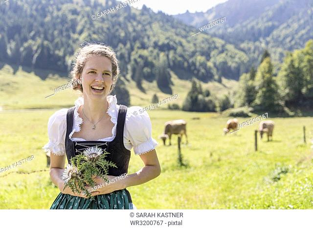 Countrywoman with dirndl holding a silver thistle