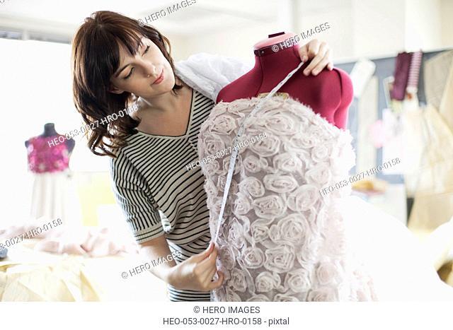 designer measuring dress on dress form