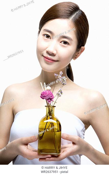 Portrait of young woman with aroma essential oil and herbal flowers