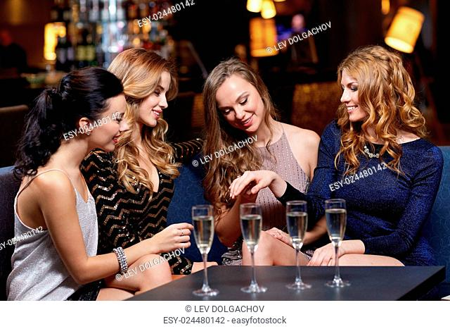 celebration, friends, bachelorette party and holidays concept - happy woman showing engagement ring to her friends with champagne glasses at night club