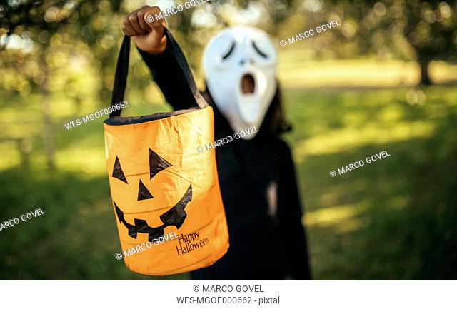 Girl masquerade with a mask holding halloween lantern