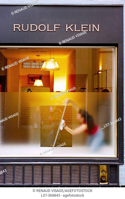 Woman cleaning display window from inside an art gallery. Cologne. Germany
